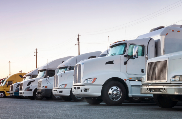 Group of semi-trucks sitting in parking lot at sunset